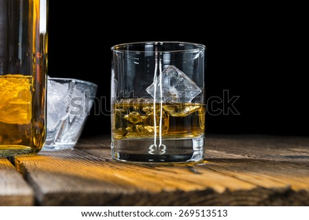 Single Malt Whiskey with Ice Cubes on wooden background - stock photo