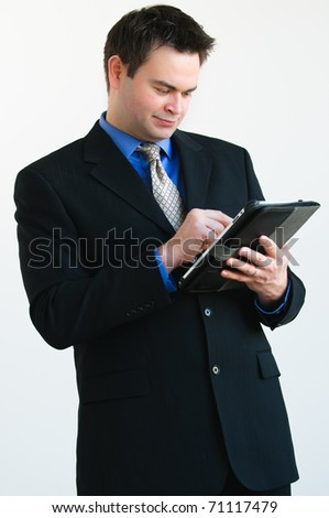 Single man in  business attire working on a tablet computer - stock photo