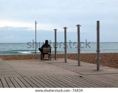 Single man sitting on a chair looking at the sea - stock photo