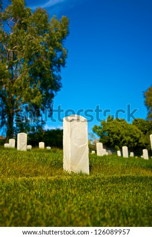 Single marble headstone stands above the grass in Los Angeles National Cemetery. - stock photo