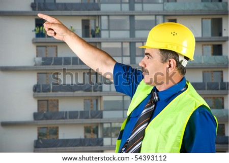 Single mature architect man pointing on site and looking up,construction with workers in background - stock photo