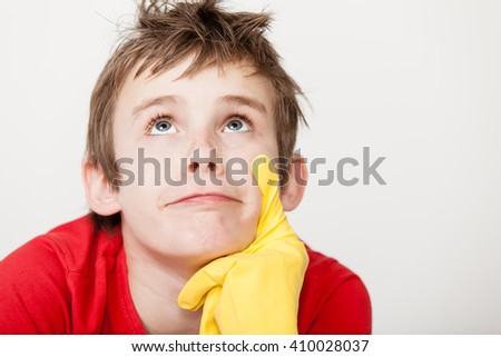 Single messy haired thinking child looking upward in red tee shirt with rubber gloved finger on chin beside copy space - stock photo