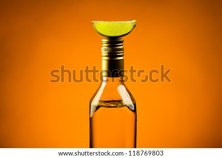 Single mexican tequila bottle with slice of lime on hot orange background - stock photo
