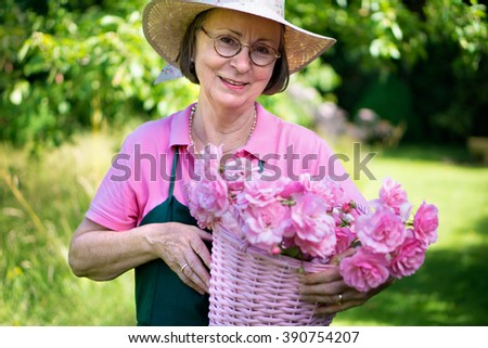 Single middle aged female gardener in hat and apron smiling while holding basket of roses in yard during summer. - stock photo