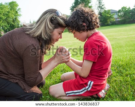 Single mother and child in humble communication through prayer with his Creator in heaven - stock photo