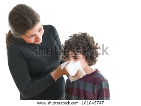 Single mother helping her son to blow his nose. Scene over white background. Hispanic family helping each other during sickness - stock photo