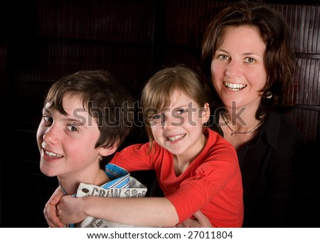 Single mother posing with her two teenager kids - stock photo
