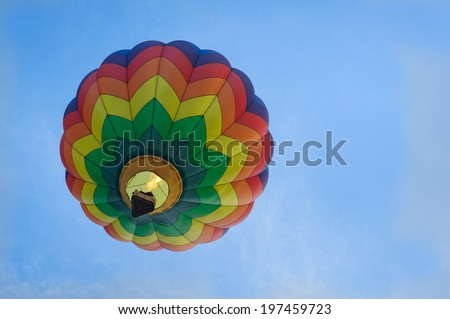 Single multi-colored hot air balloon lifts off against a blue sky. - stock photo