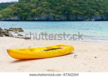 single old yellow kayak on the beach - stock photo