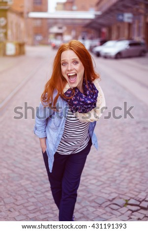 Single overjoyed young woman with blue denim shirt, white scarf, long red hair and hands in pockets walking down cobblestone street near warehouse - stock photo