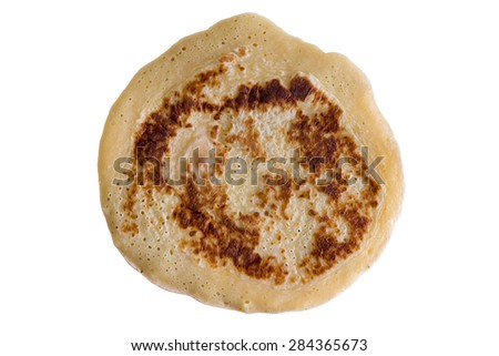 Single Pancake well cooked with various shades of the brown color areas but not burnt, above view isolated on white background - stock photo