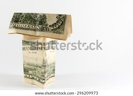 Single paper house made from US dollar bills including a 100 note - stock photo