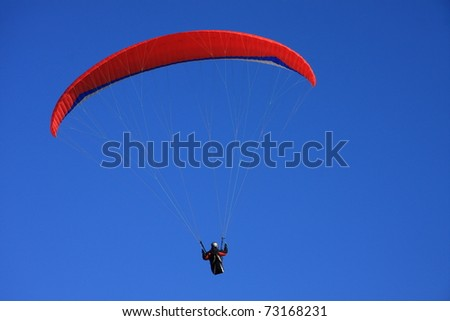 Single paraglider against blue sky - stock photo