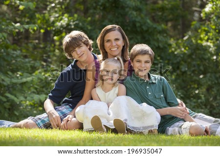 Single parent family with three children sitting  on grass lawn and leaning on mother - stock photo