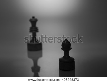 Single pawn and a blurred silhouette of a king in the dark (in black and white, retro style, selective focus on the pawn) - stock photo