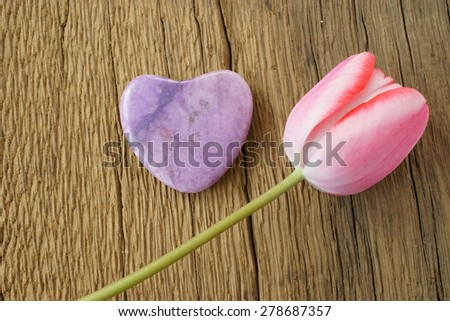 Single pink tulip and a stone heart on a rustic wooden plank - stock photo