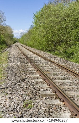 Single railway track in English countryside - stock photo