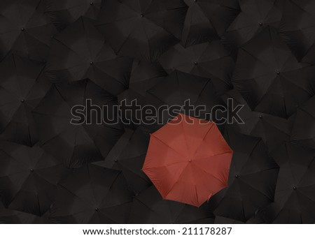 single read umbrella standing out among many black umbrellas - stock photo