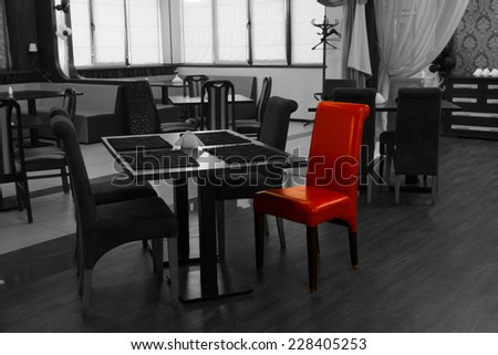 Single red chair in a greyscale nightclub interior with selective color showing modern tables and chairs - stock photo