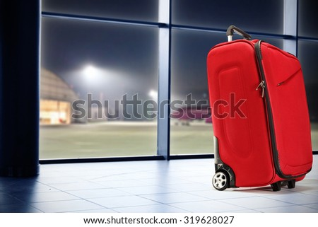 single red suitcase window of blue color and plane  - stock photo