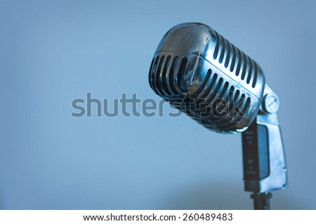 single retro microphone isolated on blue background - stock photo
