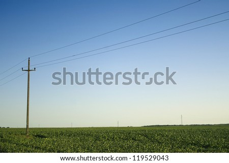 Single retro telephone pole in the field with transmission lines in the distance - stock photo