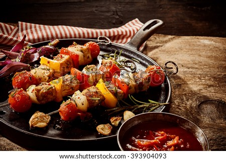 Single round black cast iron frying pan filled with seasoned kebabs on sticks with garlic, onion and rosemary next to cup of chili sauce over rustic wooden table - stock photo