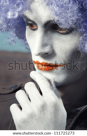 Single sad funny man with theatrical makeup and wig - stock photo