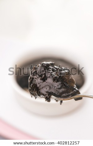 Single Serving of Molten Chocolate Cake on spoon baked in white ceramic ramekin, Hot chocolate pudding with fondant centre on plate with tablespoon, cup of tea on the table, close-up. Lava cup cake - stock photo