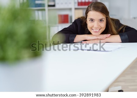 Single smiling cheerful woman in black sweater with chin on hands at table with blank copy space and plant in foreground - stock photo
