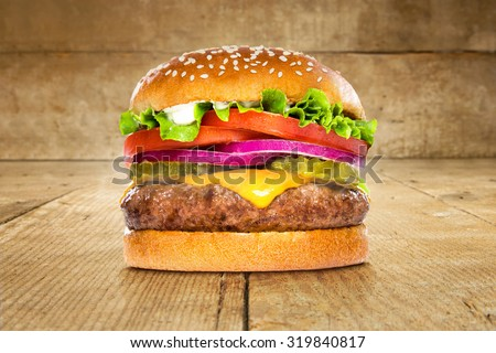 Single solo burger hamburger cheeseburger on table wooden surface delicious perfect deluxe sandwich - stock photo