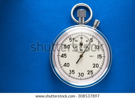 Single stopwatch closeup on blue paper background - stock photo