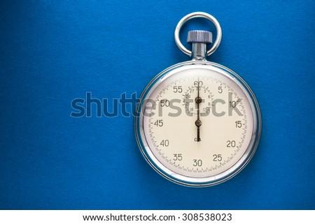 Single stopwatch closeup on blue paper background - stock photo