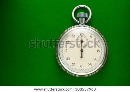 Single stopwatch closeup on green paper background - stock photo