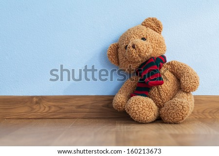 Single teddy bear on a floor in a child room - stock photo