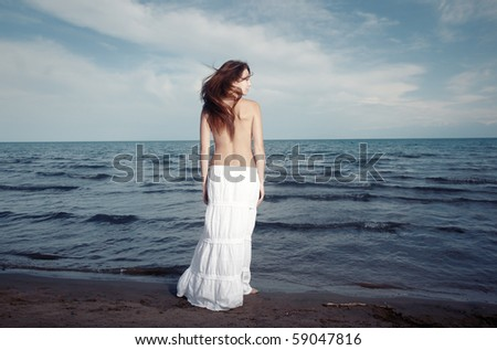 Single topless lady standing at the waving ocean. Rear view. Artistic colors added - stock photo