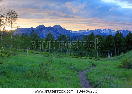 Single track trail with the Wasatch Mountains of Utah in the background. - stock photo