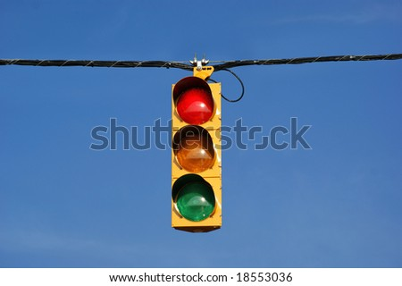 Single traffic light against blue sky background. - stock photo