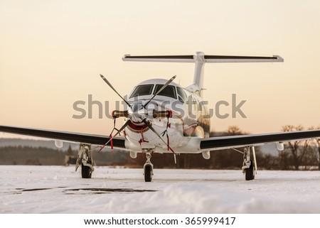 Single turboprop aircraft on winter runway during sunset. Pribram airport. Czech Republic - stock photo