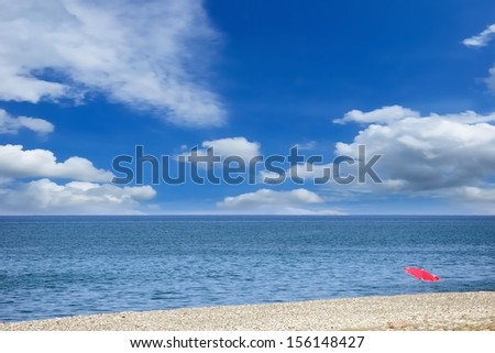 Single umbrella on the pebbly beach against the picturesque cloudy sky - stock photo