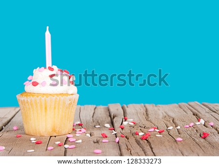 Single vanilla cupcake with pink candle and sprinkles on a pink background and wooden plank - stock photo