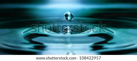 Single water drop bounces back from the water surface floating in the air and creating a nice wave in the water. - stock photo