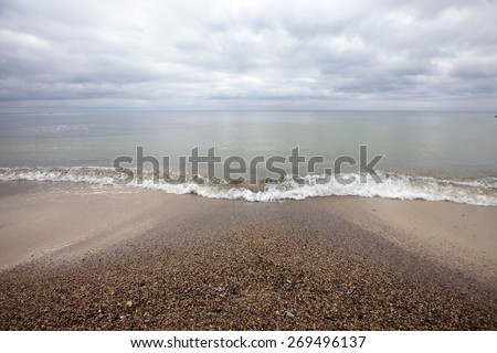 Single wave reaching sandy beach on a cloudy day at Baltic shore. Photographed at N6va, Estonia.  - stock photo