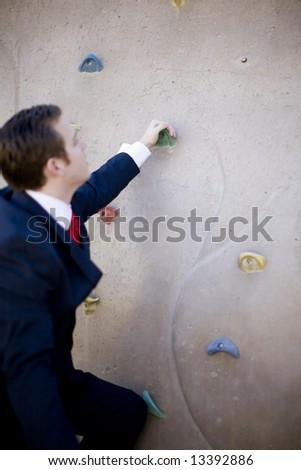 single white businessman begins to climb wall - stock photo