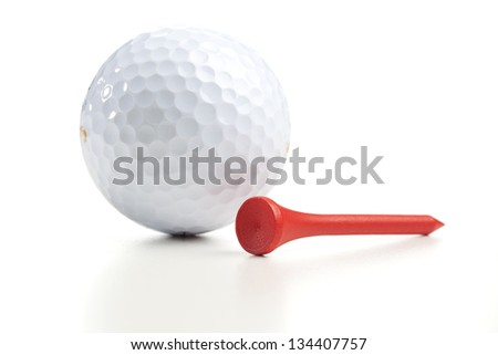 Single white golf ball and a single tee. Close up shot with shallow depth of field. - stock photo