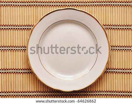 single white plate on a striped table-cloth - stock photo