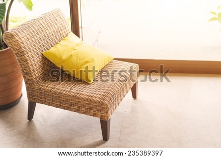 Single wickerwork chair and yellow cushion standing in front of a window alongside a potted houseplant - stock photo