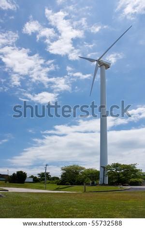 Single wind powered turbine against a blue cloudy sky - stock photo