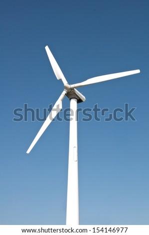 Single wind turbine on blue sky background - stock photo