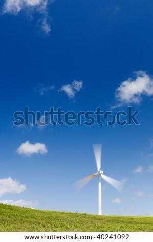Single wind turbine on grassy field over deep blue sky, alternative energy, green power, electricity generator; long exposure, motion blur on the blades - stock photo